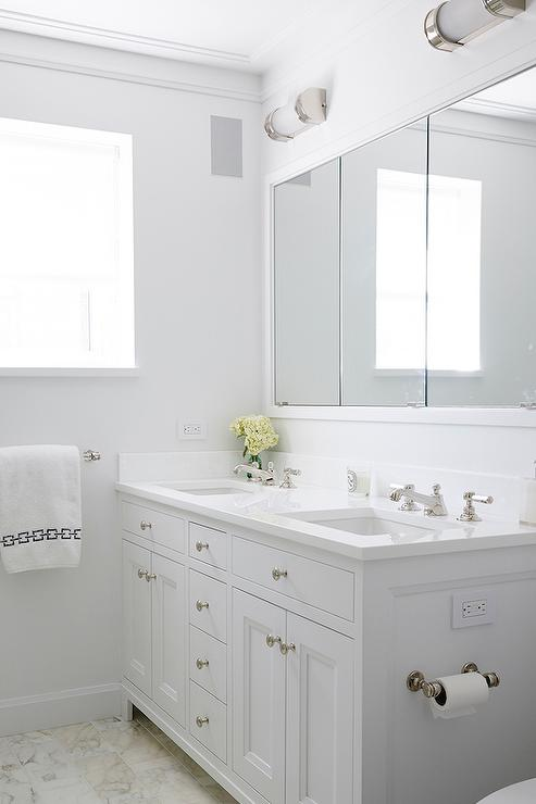 chic white bathroom features a white shaker dual vanity paired with a white quartz countertop fitted with his and her sinks and faucets under a framed