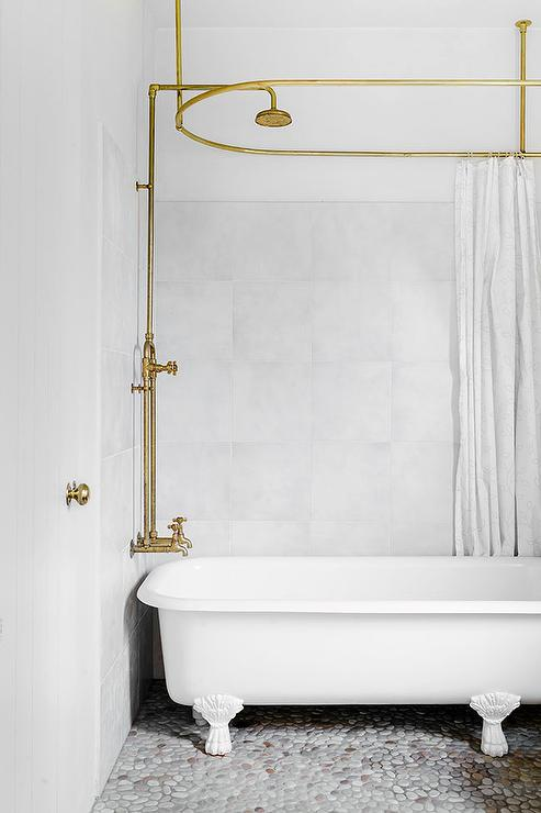 Beach Cottage Bathroom Features A White Claw Foot Tug Paired With A Gold  Exposed Plumbing Shower Kit Along With A Ceiling Mount Gold Oval Shower Rod  ...