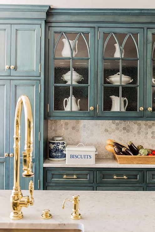 accented with gold knobs and blue lower cabinets adorned with gold