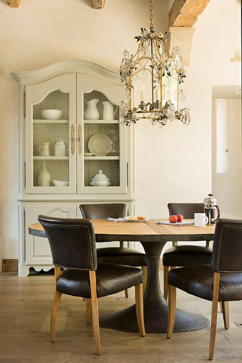 French Dining Room Features A Gold Lantern Adorned With Crystal Flowers Illuminating Restoration Hardware Aero Oval Table Lined Black Leather