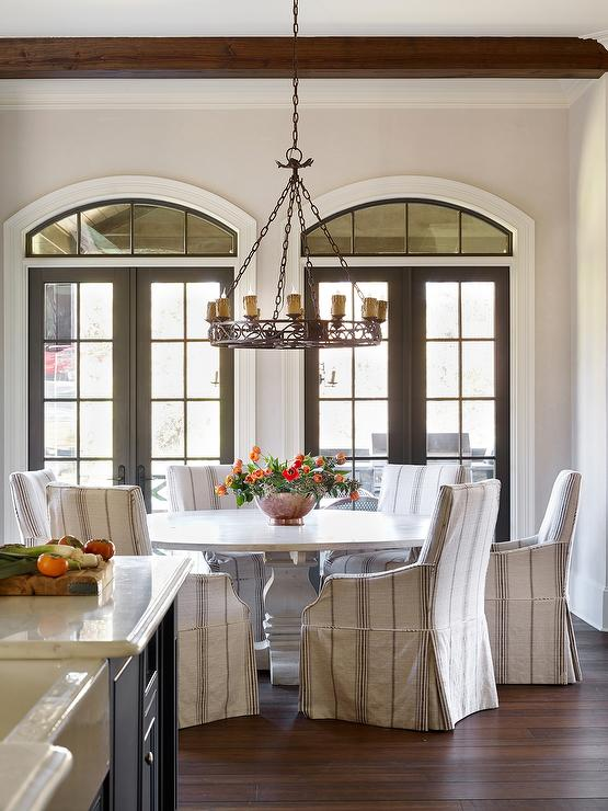 French Dining Room Features Stained Box Beam And An Iron Candelabra Illuminating A Whitewashed Round Table Surrounded By Striped Chairs