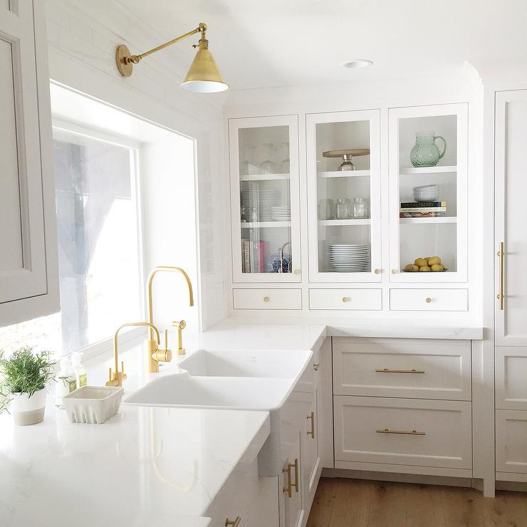 stunning kitchen features white shaker cabinets adorned with long brass pulls topped with white quartz countertops fitted with a dual apron sink and two