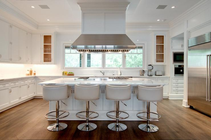 kitchen island vent hood hanging fabulous gourmet kitchen features ceiling mount vent hood suspended over an island cooktop lined with white leather barrel back counter stools silver hood kitchen island contemporary and design