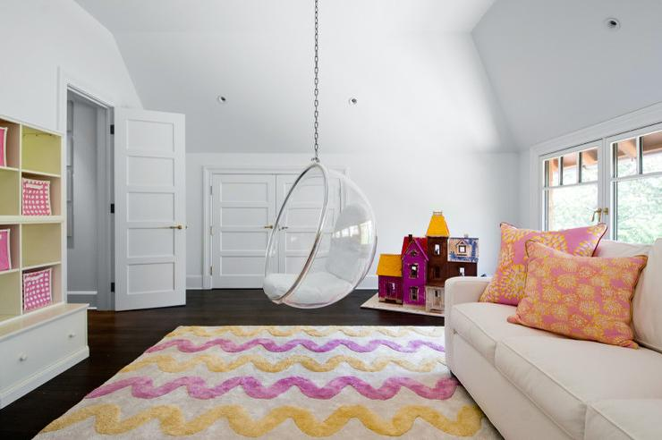 yellow and purple playroom features a clear acrylic hanging bubble chair placed dead center of the room suspended over a yellow and purple wavy rug flanked
