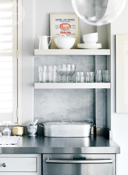 White kitchen with stainless steel floating shelves