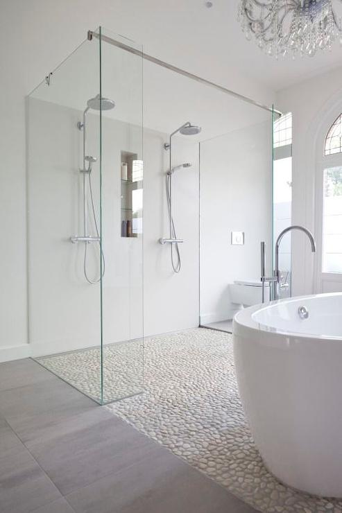 Chic Bathroom Features A Freestanding Oval Tub Paired With A Gooseneck Tub  Filler Atop A River Rock Floor Which Continues To The Walk In Shower Fitted  With ...