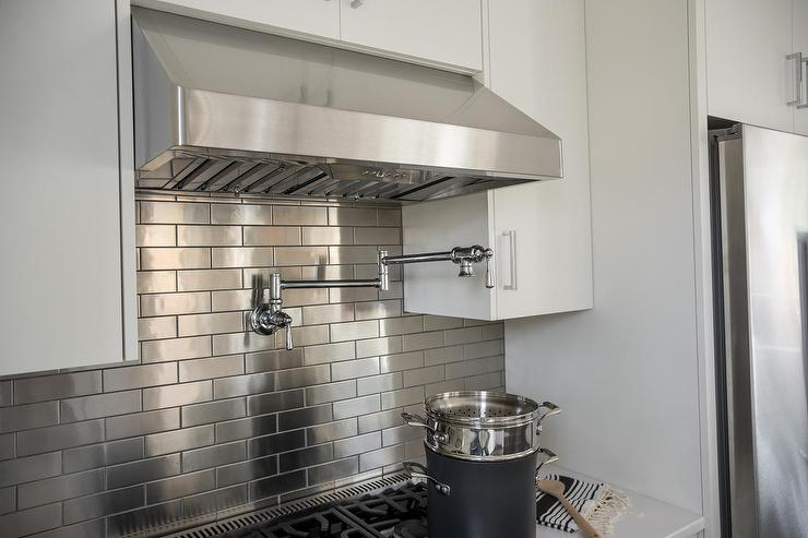 ... white quartz countertops and a stainless steel brick tiled backsplash