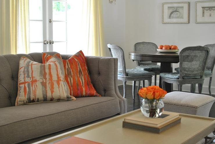 Gray and orange living room features a gray tufted high for Grey orange living room