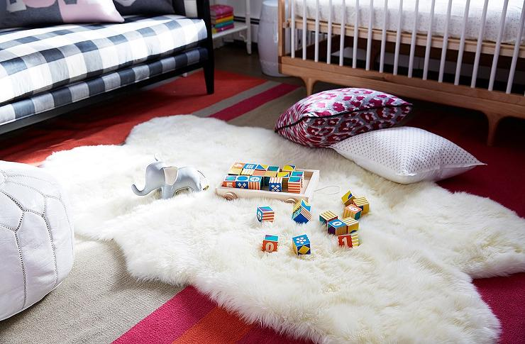 boyu0027s nursery features a midcentury modern crib placed under a window alongside a white sheepskin pelt layered atop a red orange and grey striped rug