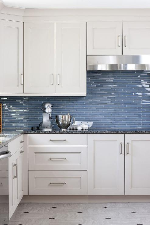 White And Blue Kitchen Features Cabinets Adorned With Satin Nickel Pulls Paired Black Countertops A Linear Glass Tiled Backsplash