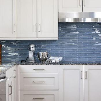 with black countertops and a linear blue glass tiled backsplash
