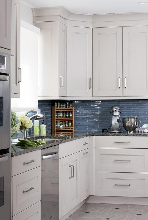 white and blue kitchen features white cabinets adorned with satin