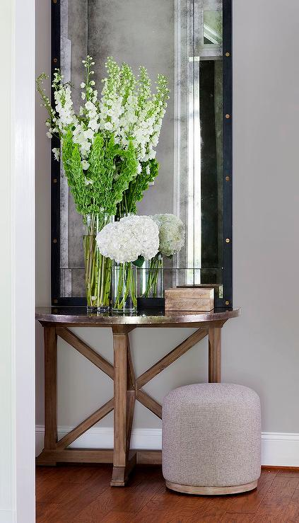 Transitional foyer boasts a wood and zinc trestle half moon table topped with fresh flowers and a tall rivets leaning mirror