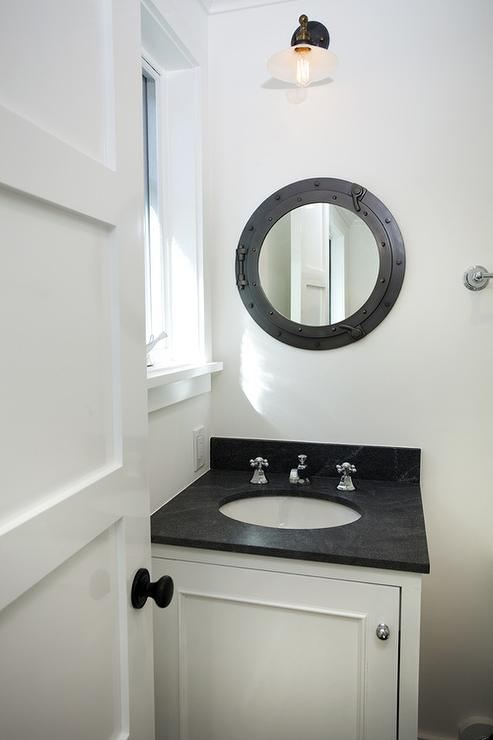 Black And White Nautical Bathroom Features A White Washstand Topped With  Honed Black Marble Under A Black Porthole Mirror Illuminated By A Single  Sconce.