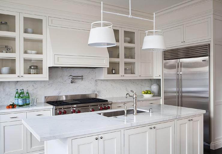 Amazing kitchen features cream cabinets paired with white marble countertops and a white marble slab backsplash. Cream Kitchen Cabinets Design Ideas
