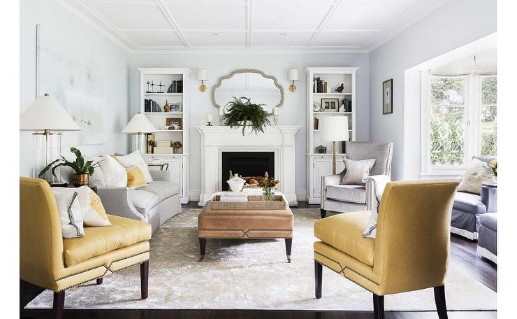 Yellow and gray living room features a curved sofa adorned with yellow  pillows alongside pair of accent chairs brass tacks from Kravet And Gray Accent Chairs Design Ideas