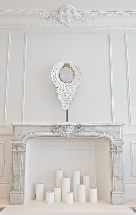 French living room features walls clad in decorative wall moldings and ornate beaded crown moldings lined with a French marble fireplace filled with candles.