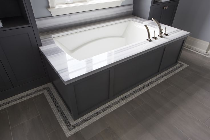 Gray wainscoted bathtub flanked by tall gray built in for Charcoal bathroom accessories