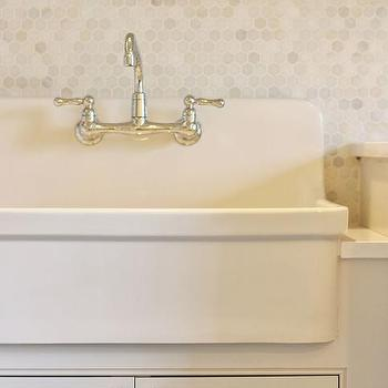 apron sink against a backdrop of an ivory marble hex tiled backsplash