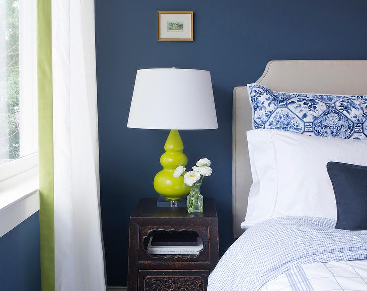 blue wall lined with a gray headboard on bed dressed in blue bedding next to an antique chinese nightstand topped with a neon green triple gourd lamp