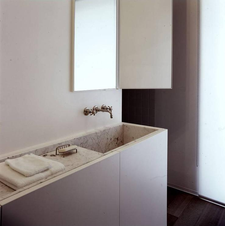 ... slim washstand fitted with a marble sink under a wall-mount faucet