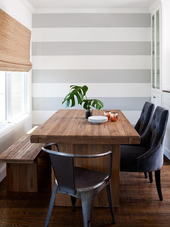 Contemporary Dining Nook Features An Accent Wall Painted With White And Gray Horizontal Stripes Alongside A Reclaimed Wood Table Lined