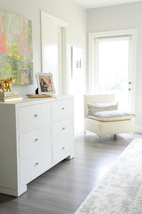 lovely bedroom features a pink and gray abstract art piece placed above a white 6 drawer dresser atop gray wash floors