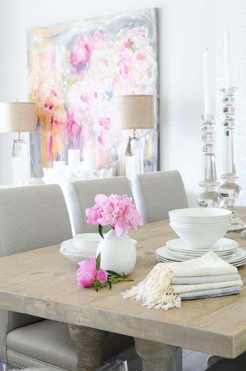 pink dining room with round rclaimed wood dining table with