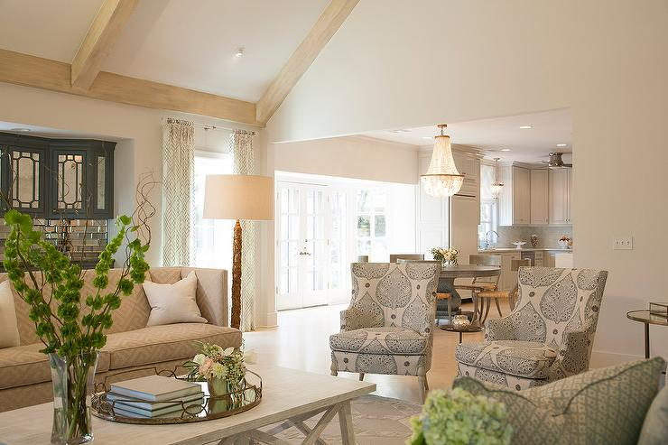 Beautiful Living Room Features A Vaulted Ceiling Lined With Light Wood Beams Shelter Back Sofa Upholstered In Tan Greek Key Fabric Facing Whitewashed