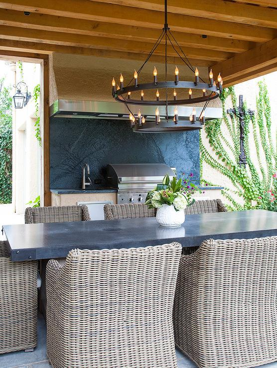 Amazing Covered Patio Features A Zinc Dining Table Lined With Wicker Dining  Chairs Illuminated By A Round Tiered Iron Candelabra Chandelier.