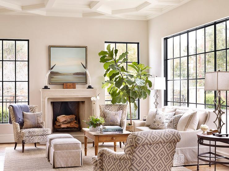 Beautiful Living Room Features A Geometric Coffered Ceiling Over Limestone Fireplace Accented With Black And White Horns Art Flanked By Steel Windows