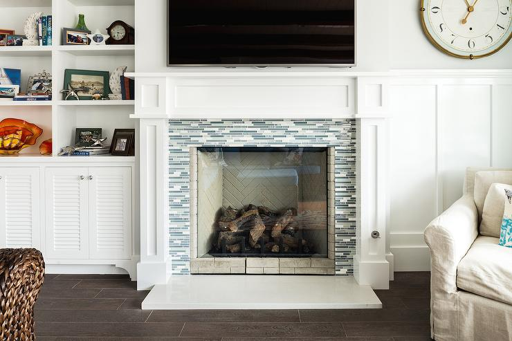 Cottage living room features a white fireplace mantle adorned with a blue and gray glass tile surround under a tv flanked by built-in bookcases and cabinets to the left and board and batten clad walls lined with a natural linen reading chair to the right.