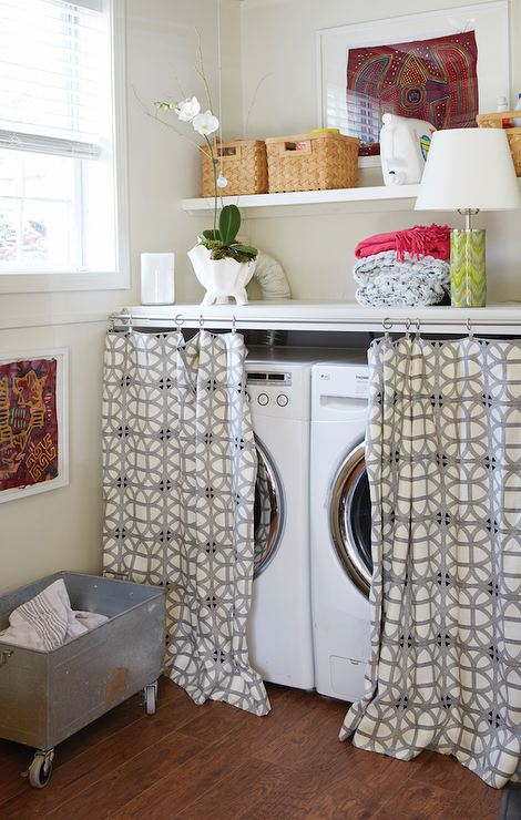Lake House Laundry Room Features A White Front Load Washer And Dryer Tucked  Under A Countertop Hidden Behind Curtains.