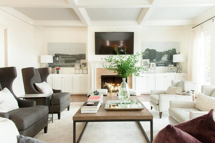 Chic living room features a coffered ceiling over a white fireplace mantle under a flatscreen TV flanked by built-in cabinets under black and white art.