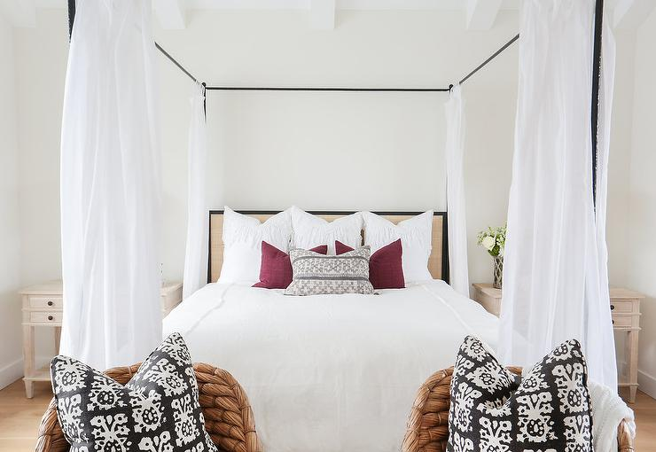 Cottage Bedroom Features An Iron Canopy Bed Fitted With A Tan Headboard Accented White Panels Flanked By Light Wood Farmhouse Nightstands Alongside