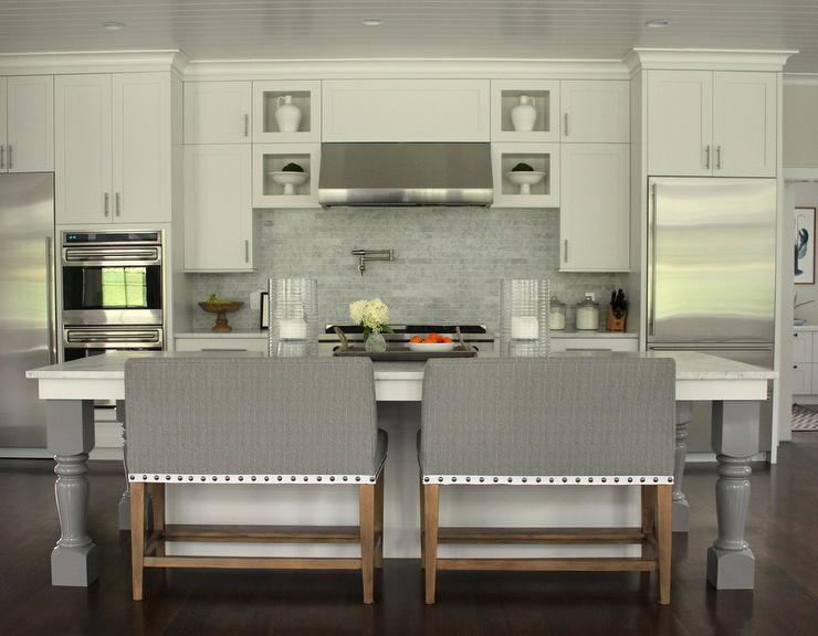 Amazing kitchen features a white center island with gray turned legs lined with side by side gray benches with nailhead trim in lieu of counter stools. : bench counter stool - islam-shia.org