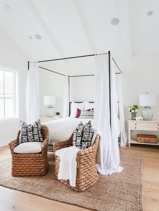 Chi cottage bedroom features a vaulted ceiling with white wood beams over an iron canopy bed fitted with a tan headboard accented with white sheers flanked ... & White Chairs in Front of Gray Wood Canopy Bed - Transitional - Bedroom