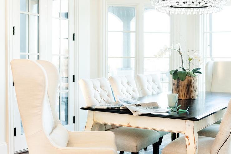 white french dining table with black top and white tufted dining chairs