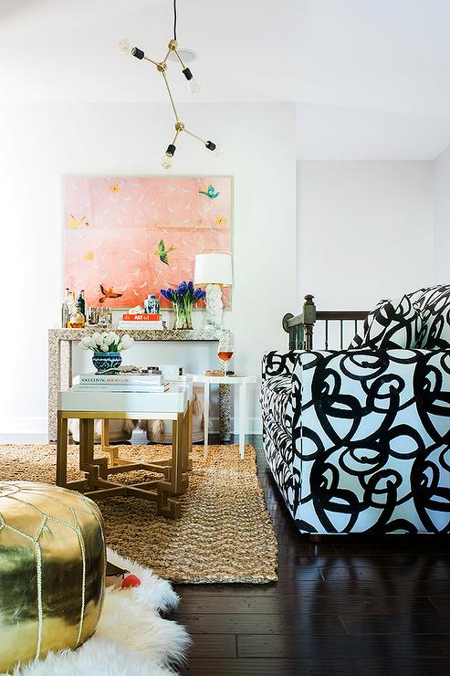 Chic Living Room Boasts A Black And White Abstract Sofa Facing Pair Of Side By Gold Bunching Tables Cleo Atop Jute Rug
