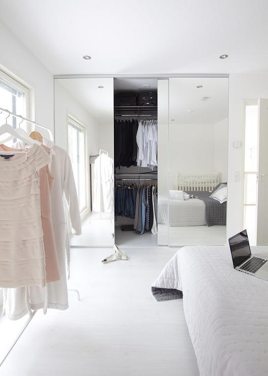 and gray quilt situated across from a clothes rack placed in front of a window alongside a closet finished with sliding mirrored doors