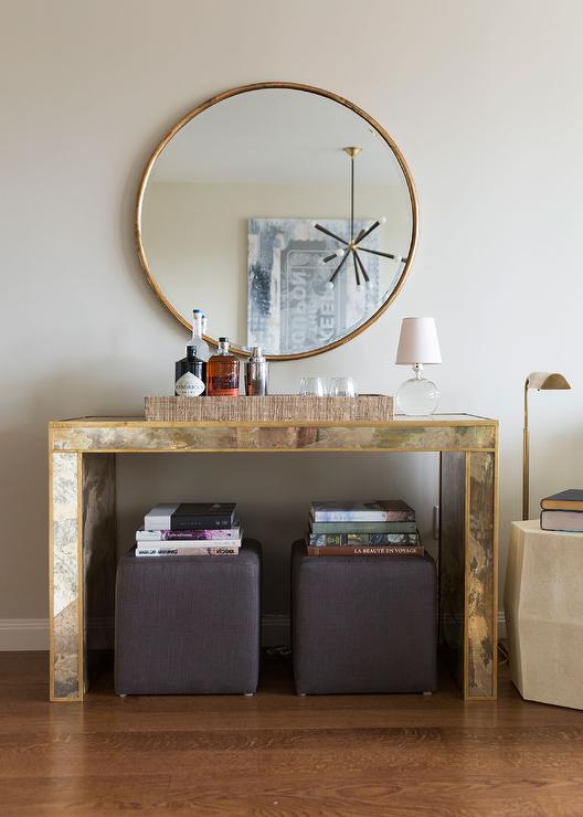 chic living room boasts a wisteria gilt minimalist mirror placed above a gold antiqued mirrored console table worlds away madison g console table