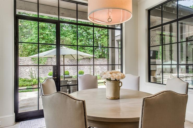 Features A Jonathan Adler Maurice Pendant Illuminating Round Dining Table Lined With Tan Camelback Chairs Accented Brass Nailhead Trim