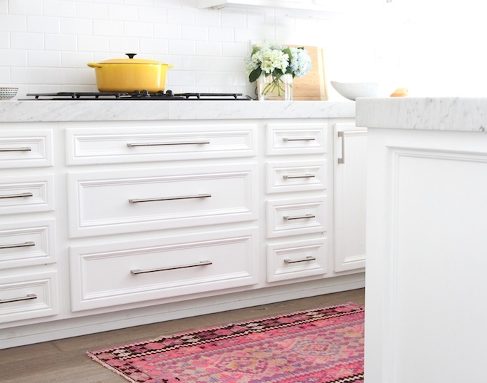 White kitchen with pink accents features white shaker cabinets adorned