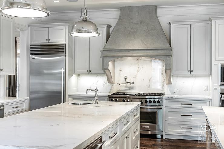 Stunning Kitchen Boasts White Shaker Cabinets Paired With White Stone  Countertops And Matching Backsplash. MDD Architects · Island Prep Sink
