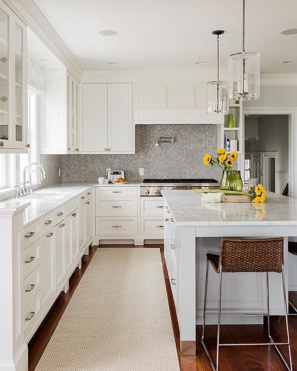cabinets paired with white marble countertops and a grey marble
