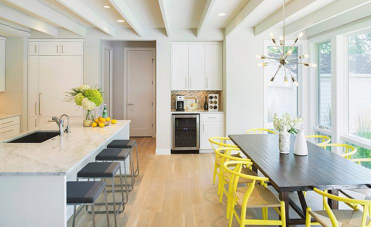 Contemporary Kitchen Features A Long Center Island Lined With Backless Gray  Counter Stools Situated Across From Dark Stained Dining Tabled Lined With  Yellow ...