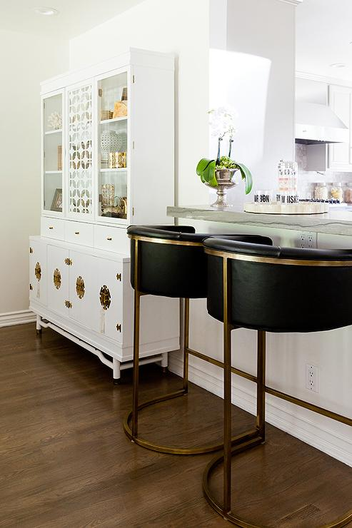 kitchen bar is lined with black and gold barrel back barstools arteriors calvin barstools situated next to a white and gold chinoiserie china