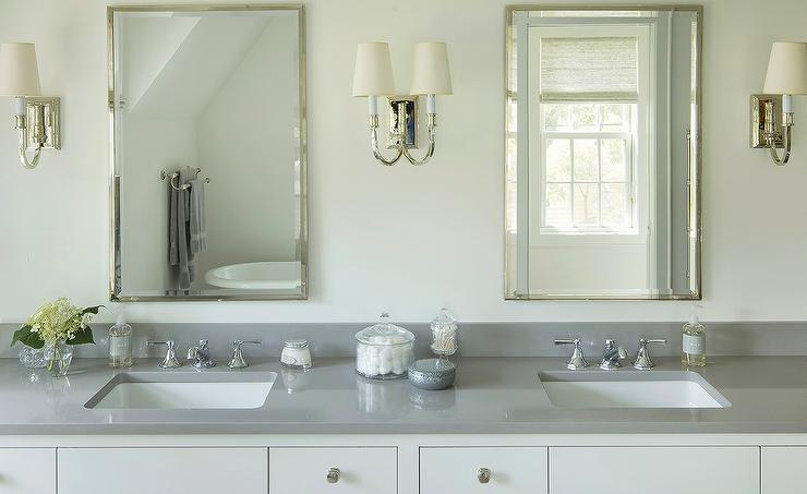 Elegant bathroom features a white washstand adorned with nickel knobs  topped with gray quartz fitted with his and her sinks under polished nickel. Grey Quartz Bathroom Countertop Design Ideas