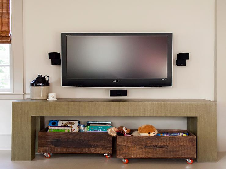 Family Room Boasts A Pair Of Wood Rolling Toy Carts Tucked Under A  Waterfall Table Under A Flatscreen TV.