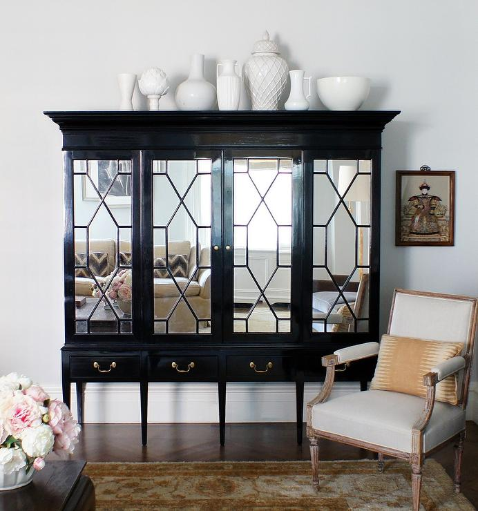 Elegant Living Room Features A Black Armoire Accented With Mirrored Doors Atop Sleek Legs Topped Collection Of White Pottery Alongside Bergere